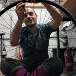"Tynan tightening the spokes on a new 36"" wheel"